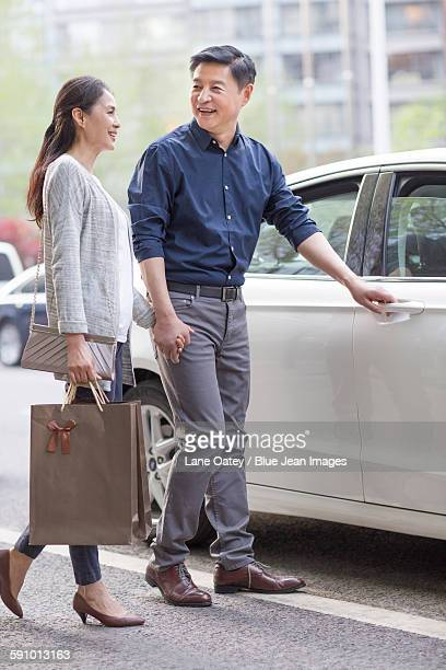 Happy mature couple and car