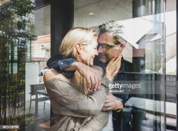 happy mature couple behind windowpane at home - heterosexuelles paar stock-fotos und bilder