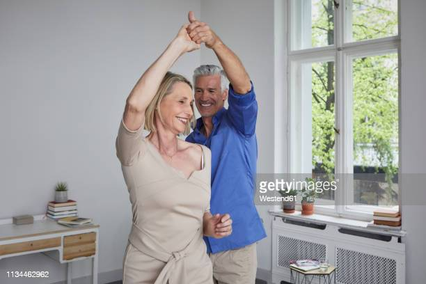 happy mature couple dancing at home - 50 59 years stock pictures, royalty-free photos & images
