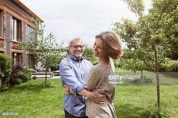 Happy mature couple dancing in garden