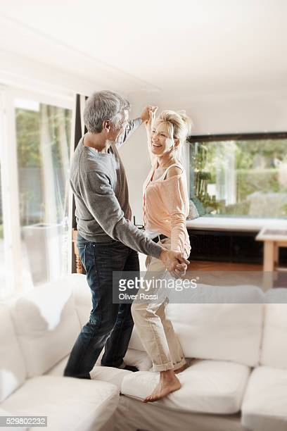 Happy mature couple dancing in living room