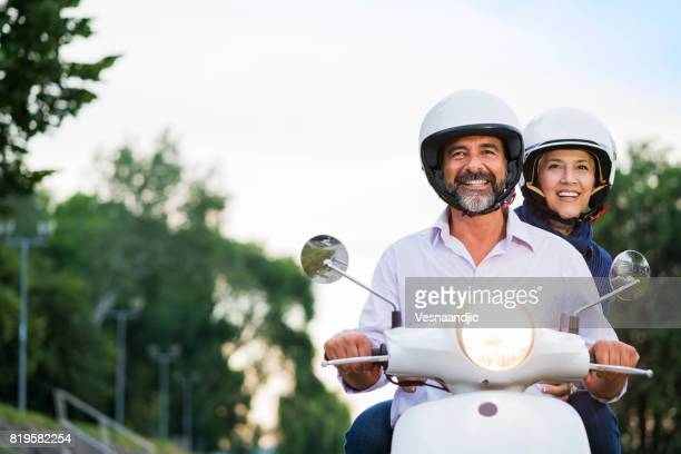 Happy Mature Couple Driving Scooter