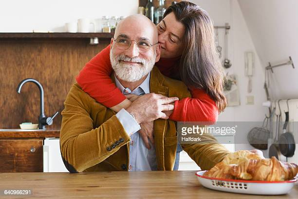 Happy mature couple embracing at home