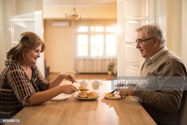 Gelukkig ouder paar hebben van een maaltijd bij de eettafel thuis.