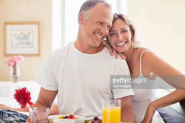 happy mature couple having breakfast in bed - 40 49 years stock pictures, royalty-free photos & images