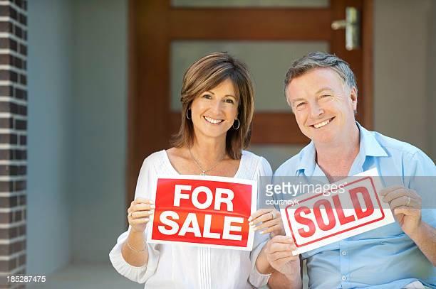 Heureux couple d'âge mûr tenant pour la vente et vendu les panneaux