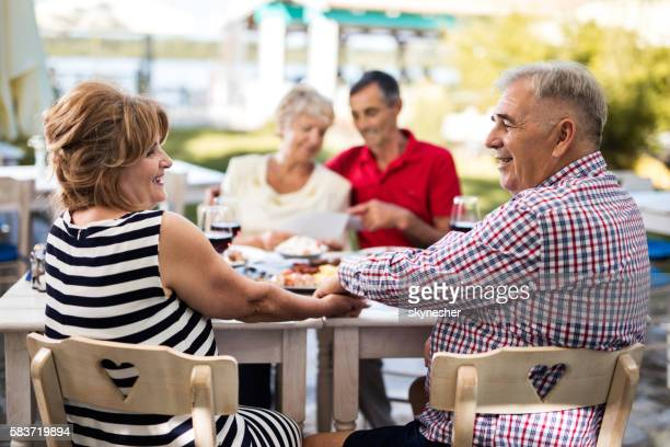 Happy mature couple holding hands and talking in the restaurant.