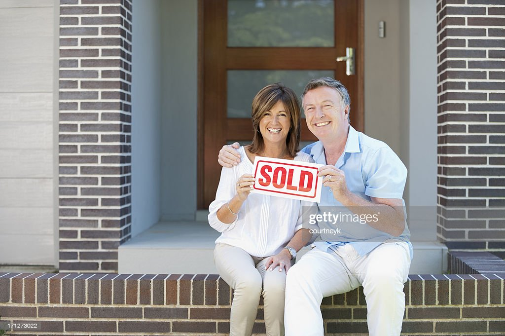 Happy mature couple holding sold sign : Stock Photo