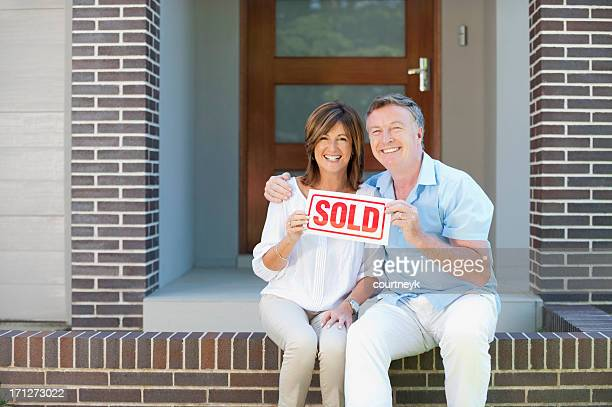 happy mature couple holding sold sign - vendor stock pictures, royalty-free photos & images