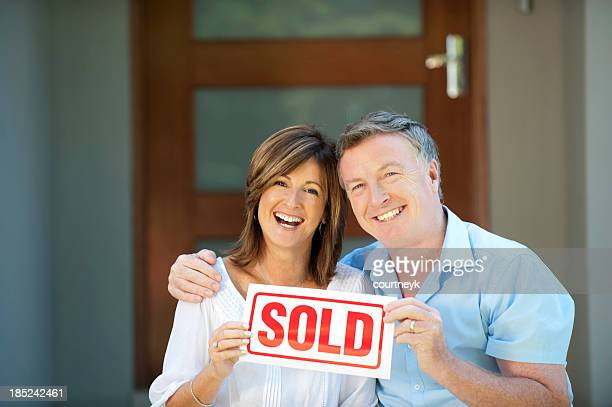 happy mature couple holding sold sign - selling stock pictures, royalty-free photos & images