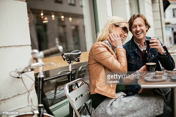happy mature couple in cafe - stadsstraat stockfoto's en -beelden