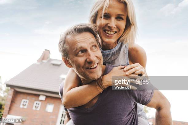 Happy mature couple in front of their home