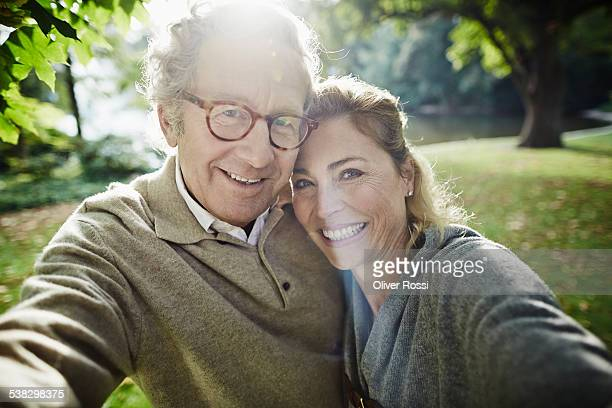 Happy mature couple in park looking at camera