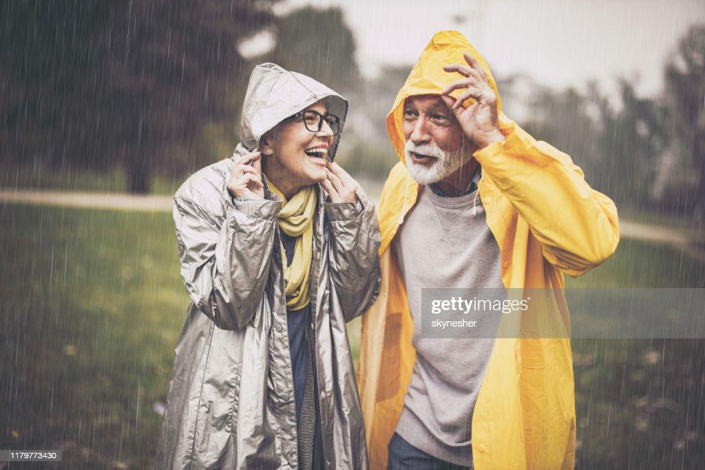 Felice coppia matura in impermeabili durante la pioggia nel parco. : Foto stock