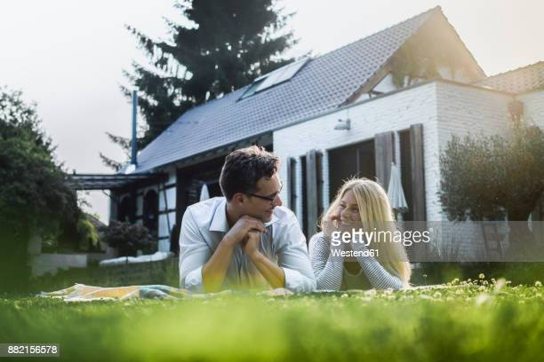 happy mature couple lying on meadow in front of their house - eigenheim stock-fotos und bilder