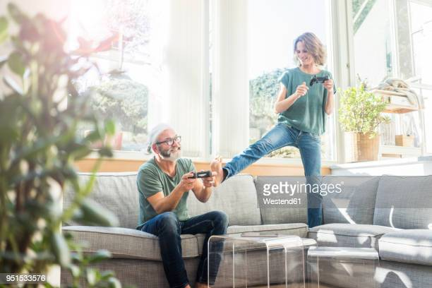 Happy mature couple on couch at home playing video game