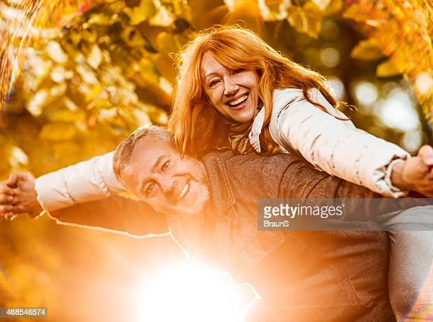 Happy mature couple piggybacking in the park.