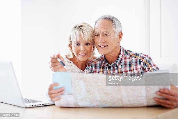 Happy mature couple planning vacation with map, laptop on table
