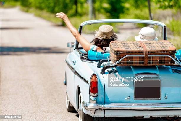happy mature couple portrait on a road trip vacation driving a vintage car - vintage car stock pictures, royalty-free photos & images