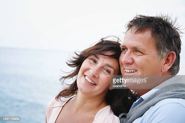A happy mature couple posing in front of the sea