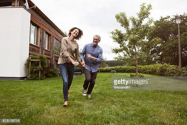 Happy mature couple running in garden
