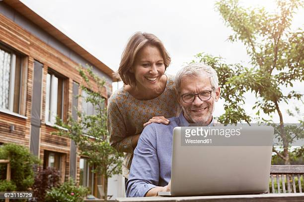 Happy mature couple sharing laptop in garden