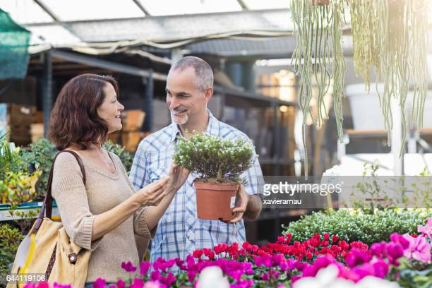Happy mature couple shopping at plant nursery