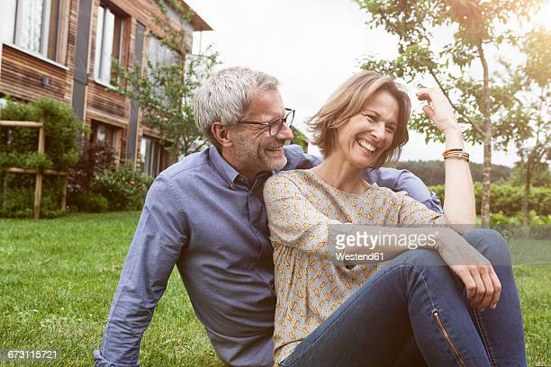 Happy mature couple sitting in garden