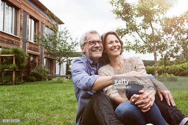 Happy mature couple sitting in garden