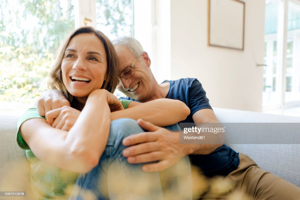 Happy mature couple sitting on couch at home : Stock-Foto
