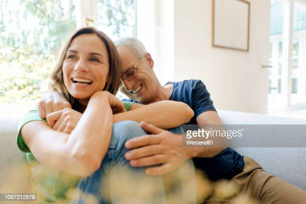happy mature couple sitting on couch at home - couple stock-fotos und bilder
