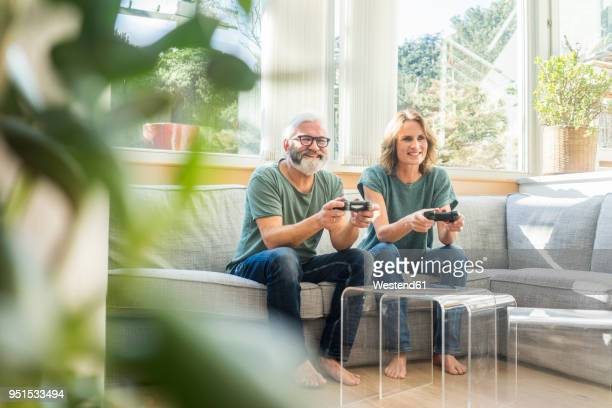 Happy mature couple sitting on couch at home playing video game