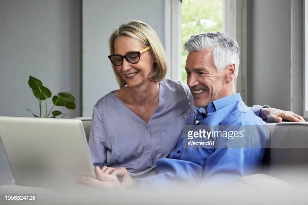 happy mature couple sitting on couch at home sharing laptop - 50 54 jahre stock-fotos und bilder