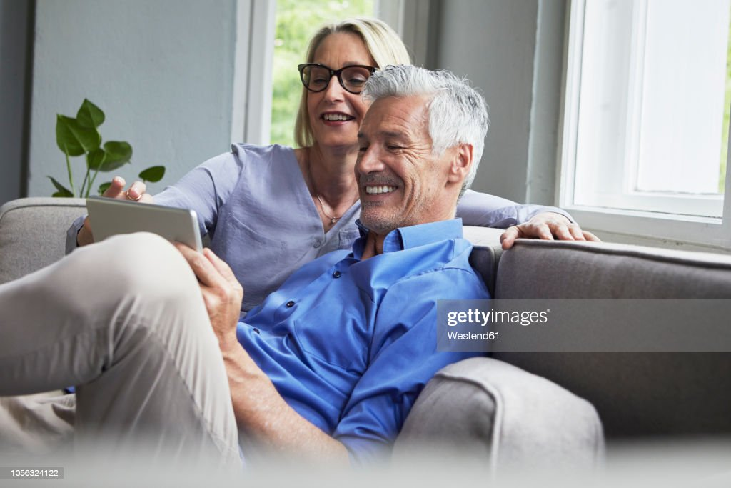 Happy mature couple sitting on couch at home sharing tablet : Stock Photo