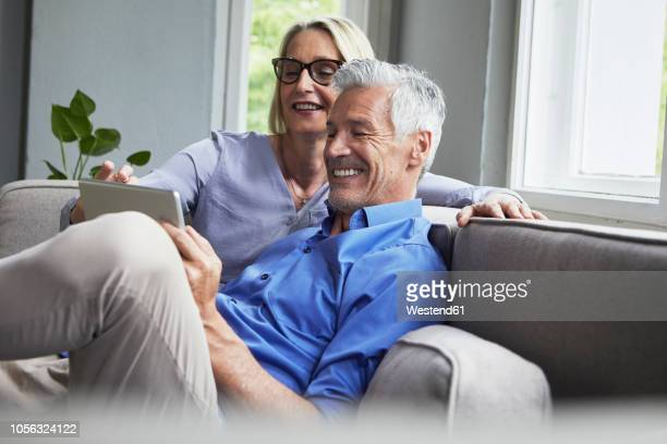 happy mature couple sitting on couch at home sharing tablet - 50 59 years stock pictures, royalty-free photos & images