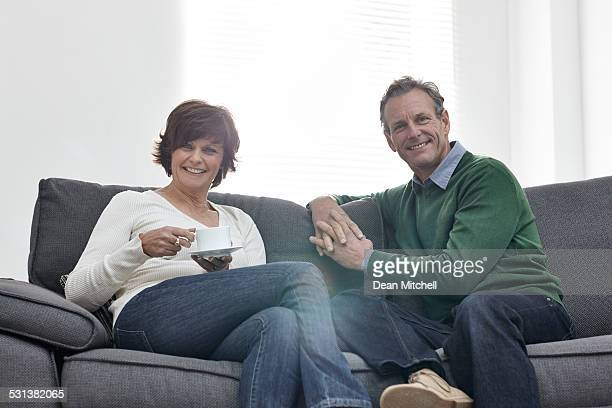 Happy mature couple sitting on sofa at home