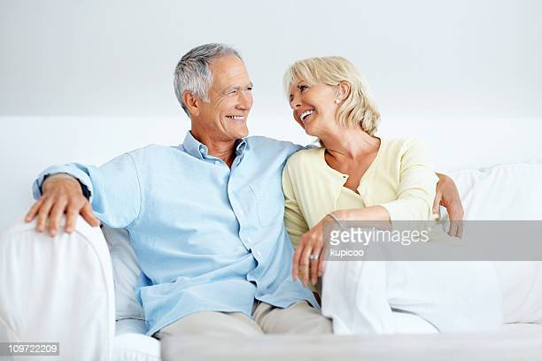 Happy mature couple sitting together in sofa at home