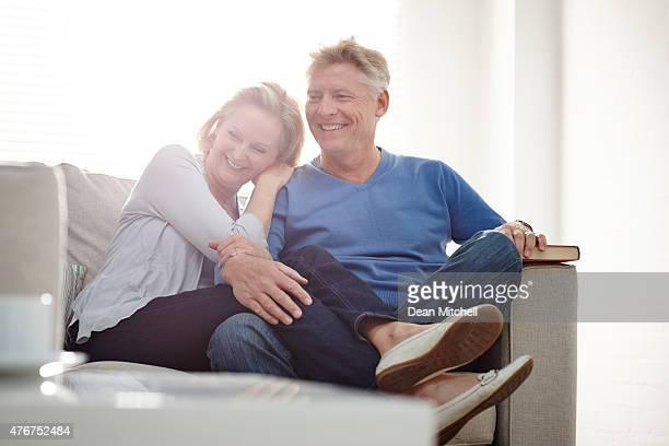 happy mature couple sitting together on couch - ouder volwassenen koppel stockfoto's en -beelden
