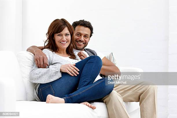 happy mature couple sitting together on sofa at home - interracial wife stock pictures, royalty-free photos & images