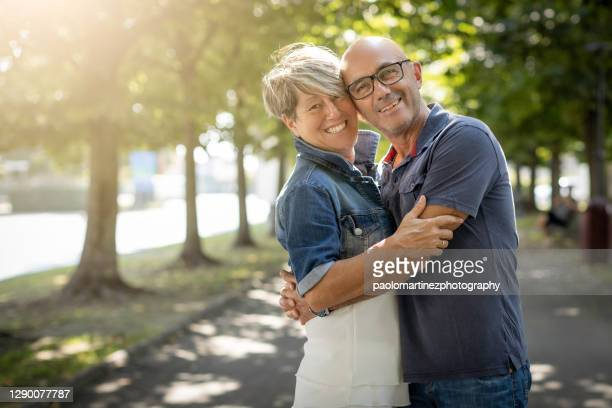 happy mature couple standing and smiling in a park - mid adult stock pictures, royalty-free photos & images
