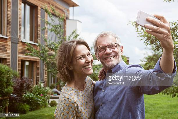 Happy mature couple taking selfie in garden