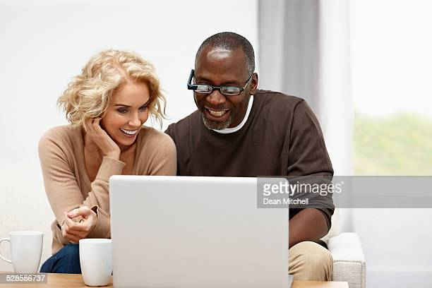 Happy mature couple using a laptop together