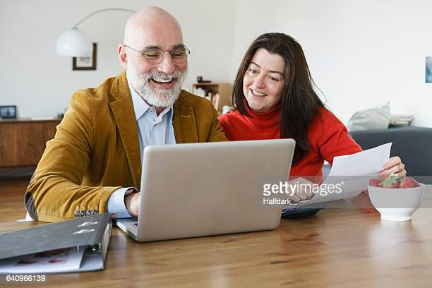 Happy mature couple using laptop on table at home