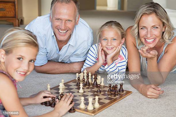 Happy mature couple watching kids play chess at home