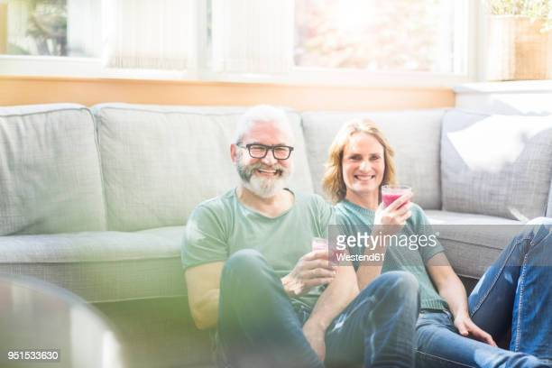 happy mature couple with healthy drinks in living room at home - 50 59 jaar stockfoto's en -beelden