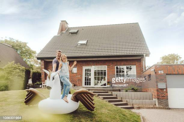happy mature couple with inflatable pool toy in garden of their home - freaky couples stock photos and pictures