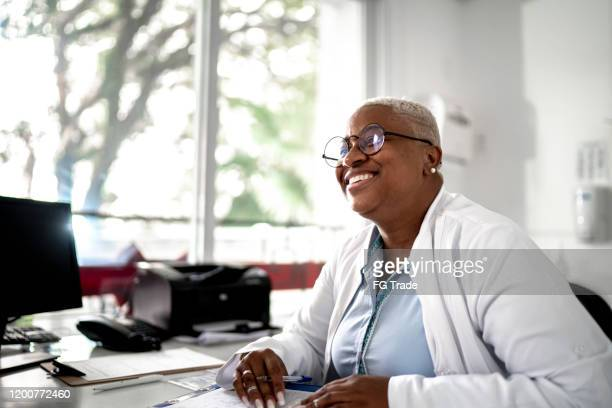 happy mature doctor woman smiling to patient on medical appointment - eye doctor stock pictures, royalty-free photos & images