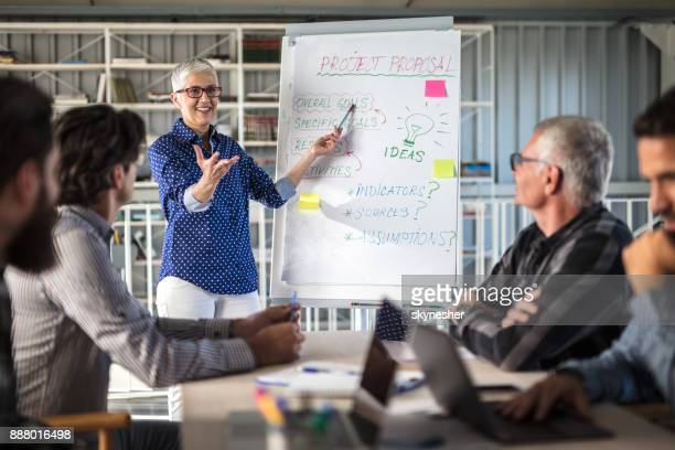 Happy mature entrepreneur talking to her team on business presentation in the office.