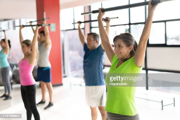 happy mature female at the gym during class working out her arms smiling - hispanolistic stock photos and pictures