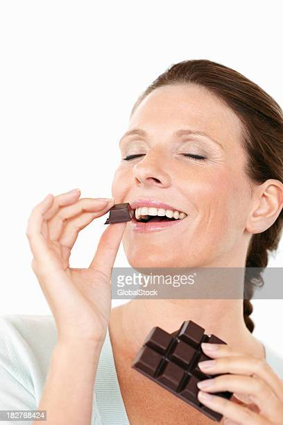 Happy mature female eating a chocolate against white
